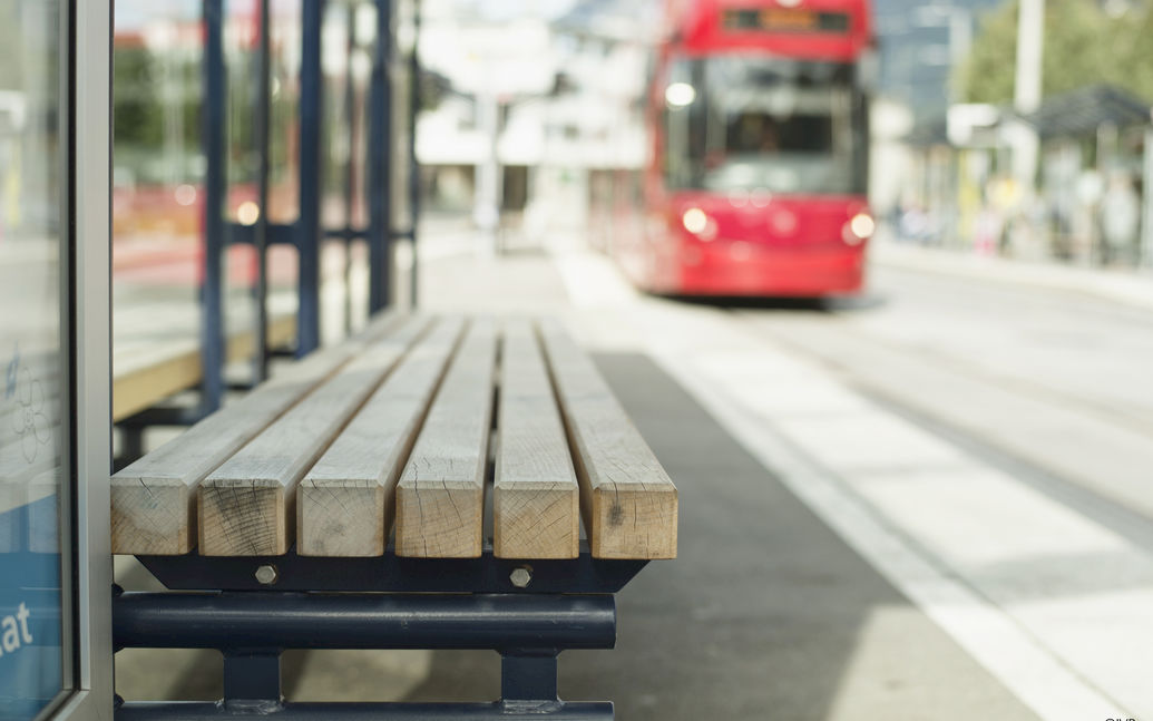 Close-up of a bench at the stop, with tram arriving at stop in background