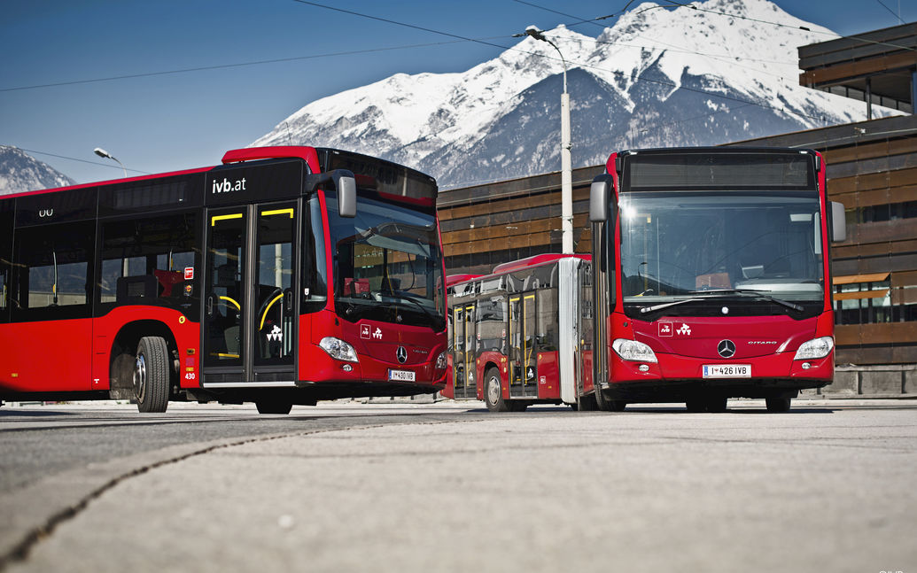 IVB buses at a stop with snowy mountains in the background